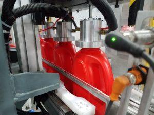 Large HDPE Bottles on conveyor going through leak testing station
